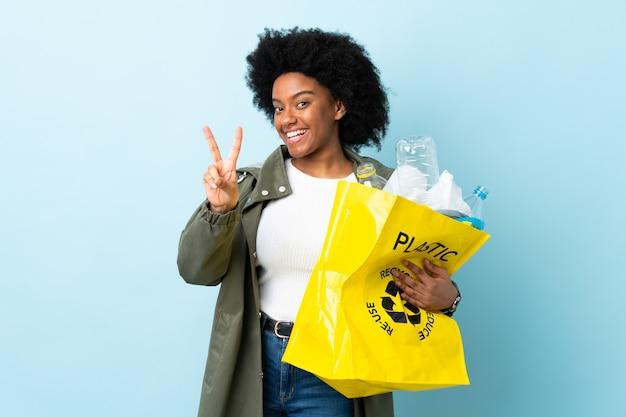 Jonge afrikaanse amerikaanse vrouw die een kringloopzak houdt die en overwinningsteken glimlacht toont