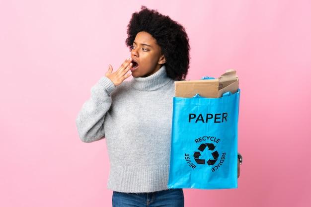 Jonge afrikaanse amerikaanse vrouw die een kringloopzak houdt die en wijd open mond met hand behandelt geeuwt