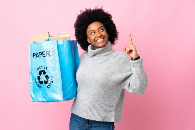 Jonge afrikaanse amerikaanse vrouw die een kringloopzak houdt die op kleurrijk wordt geïsoleerd die een groot idee benadrukt