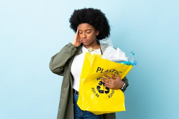 Jonge afrikaanse amerikaanse vrouw die een kringloopzak houdt die op kleurrijke achtergrond met hoofdpijn wordt geïsoleerd