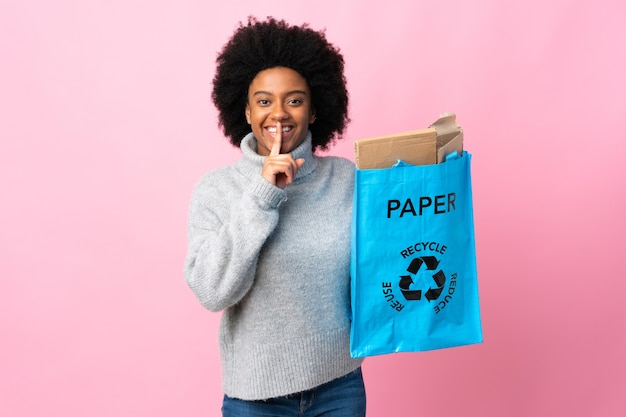 Jonge afrikaanse amerikaanse vrouw die een kringloopzak houdt die op kleurrijke achtergrond wordt geïsoleerd die een teken van stilte-gebaar toont dat vinger in mond zet