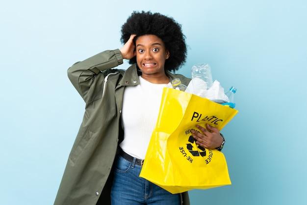 Jonge afrikaanse amerikaanse vrouw die een kringloopzak houdt die op kleurrijke achtergrond wordt geïsoleerd die zenuwachtig gebaar doet