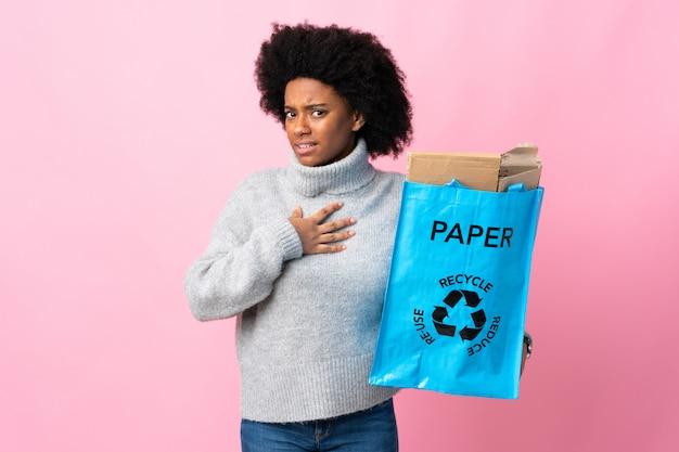 Jonge afrikaanse amerikaanse vrouw die een kringloopzak houdt die op kleurrijke muur wordt geïsoleerd die aan zich richt