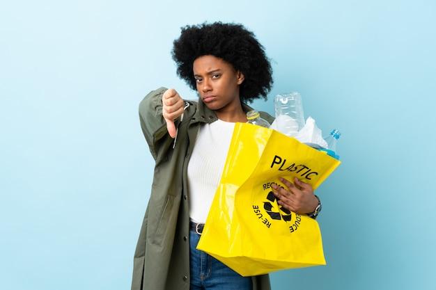 Jonge afrikaanse amerikaanse vrouw die een kringloopzak houdt die op kleurrijke muur wordt geïsoleerd die duim neer met negatieve uitdrukking toont