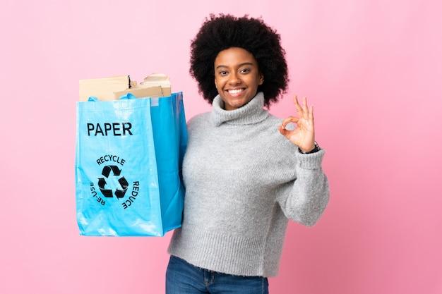 Jonge afrikaanse amerikaanse vrouw die een kringloopzak houdt die op kleurrijke muur wordt geïsoleerd die ok teken met twee handen toont