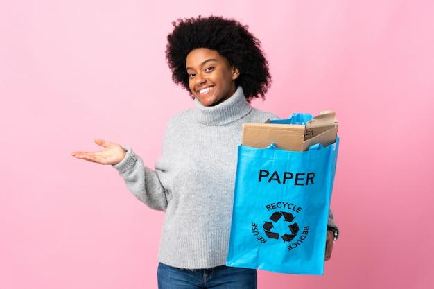 Jonge afrikaanse amerikaanse vrouw die een kringloopzak op kleurrijke muur houden die een idee voorstellen terwijl het kijken naar glimlachen