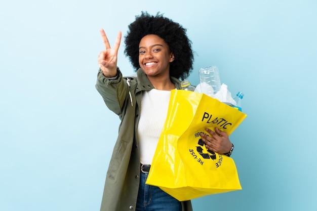 Jonge afrikaanse amerikaanse vrouw die een kringloopzak op kleurrijke muur houden die en overwinningsteken glimlachen tonen