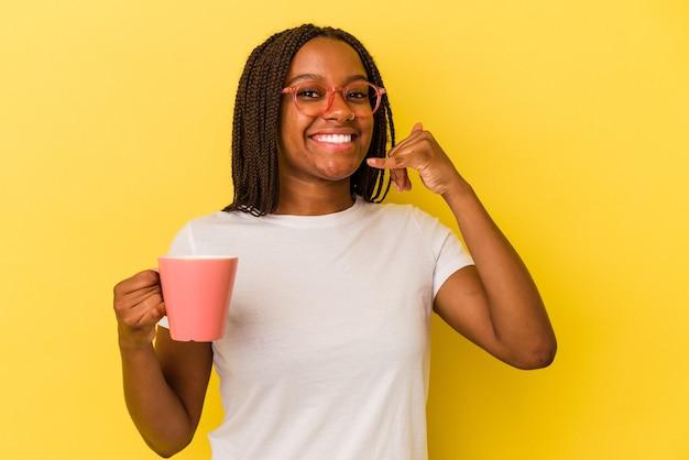 Jonge afrikaanse amerikaanse vrouw die een mok houdt die op gele achtergrond wordt geïsoleerd die een mobiel telefoongesprekgebaar met vingers toont.