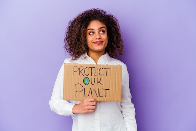 Jonge afrikaanse amerikaanse vrouw die een plakkaat van de meisjesmacht houdt dat op purpere achtergrond wordt geïsoleerd die droomt van het bereiken van doelstellingen en doeleinden