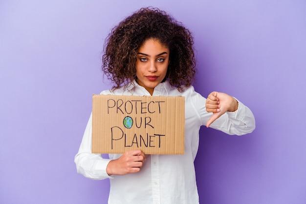 Jonge afrikaanse amerikaanse vrouw die een plakkaat van de meisjesmacht houdt dat op purpere achtergrond wordt geïsoleerd die een afkeergebaar toont, duim omlaag. meningsverschil concept.