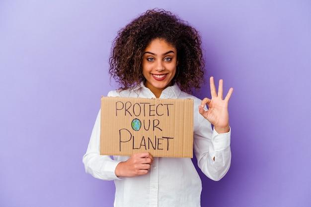Jonge afrikaanse amerikaanse vrouw die een plakkaat van de meisjesmacht houdt dat op purpere achtergrond wordt geïsoleerd vrolijk en zelfverzekerd ok gebaar toont.