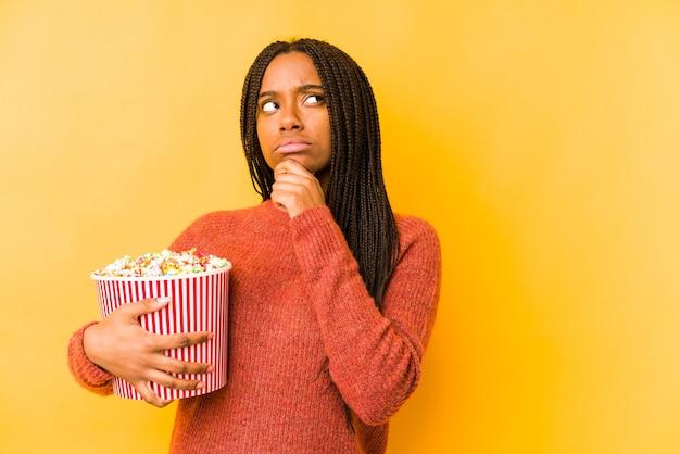 Jonge afrikaanse amerikaanse vrouw die een popcorn geïsoleerd houdt die zijwaarts kijkt met twijfelachtige en sceptische uitdrukking.