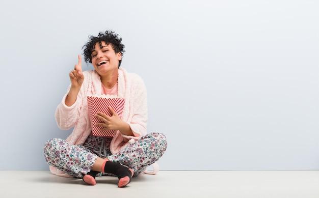 Jonge afrikaanse amerikaanse vrouw die een popcornemmer houdt die nummer één met vinger toont.