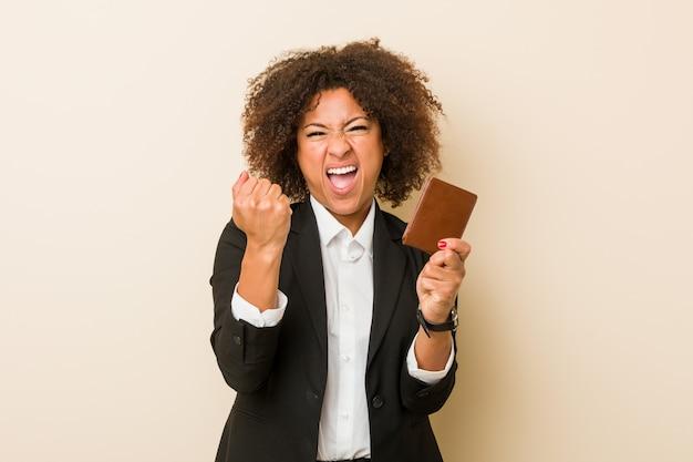 Jonge afrikaanse amerikaanse vrouw die een portefeuille onbezorgd en opgewekt toejuichen houdt. overwinning concept.