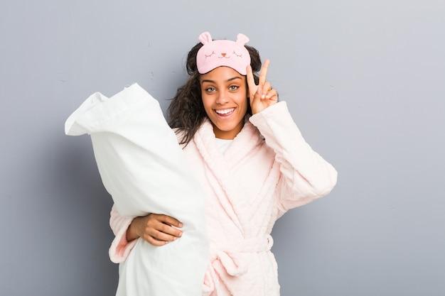 Jonge afrikaanse amerikaanse vrouw die een pyjama en een slaapmasker draagt die een hoofdkussen houdt dat overwinningsteken toont en breed glimlacht.