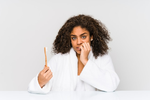 Jonge afrikaanse amerikaanse vrouw die een tandenborstel houdt die vingernagels bijt, zenuwachtig en zeer angstig.