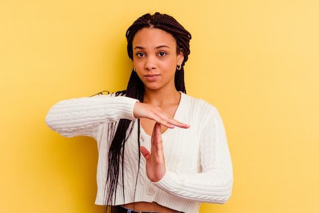 Jonge afrikaanse amerikaanse vrouw die een time-outgebaar toont.