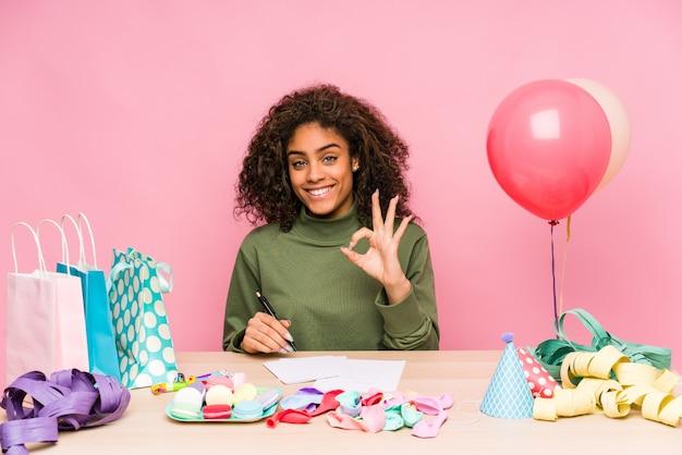 Jonge afrikaanse amerikaanse vrouw die een verjaardag vrolijk en zeker plannen die ok gebaar tonen.
