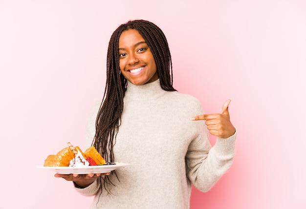Jonge afrikaanse amerikaanse vrouw die een wafelpersoon houdt die met de hand aan een overhemds lege ruimte, trots en zeker richten
