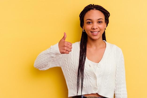 Jonge afrikaanse amerikaanse vrouw die en duim glimlacht opheft