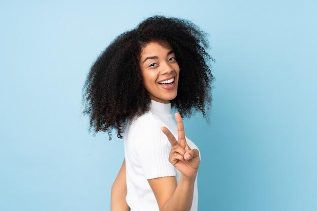 Jonge afrikaanse amerikaanse vrouw die en overwinningsteken glimlacht toont