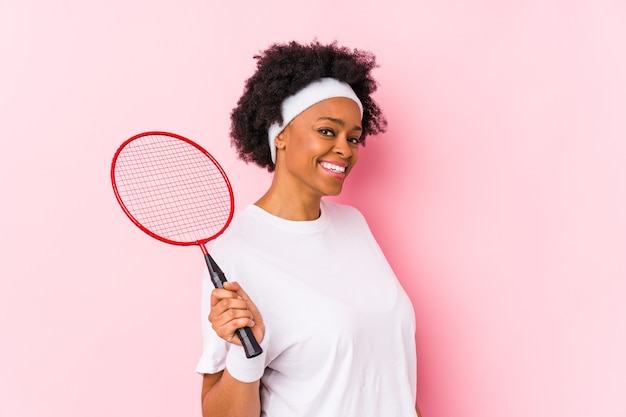 Jonge afrikaanse amerikaanse vrouw die geïsoleerd badminton speelt kijkt opzij glimlachend, vrolijk en aangenaam.
