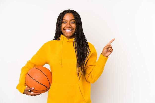 Jonge afrikaanse amerikaanse vrouw die geïsoleerd basketbal speelt en opzij glimlacht wijst, iets op lege ruimte toont.