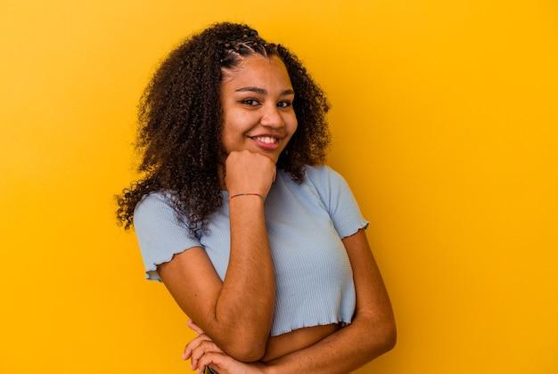 Jonge afrikaanse amerikaanse vrouw die gelukkig en zelfverzekerd glimlacht, kin met hand aanraakt.