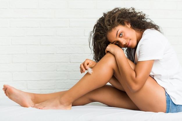 Jonge afrikaanse amerikaanse vrouw die haar benenhuid behandelt