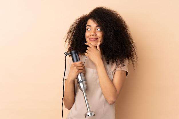 Jonge afrikaanse amerikaanse vrouw die handmixer op beige muur gebruiken die een idee denken