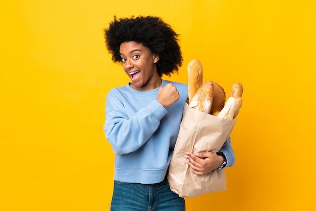 Jonge afrikaanse amerikaanse vrouw die iets brood koopt dat op geel wordt geïsoleerd die een overwinning viert