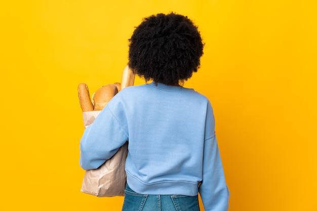 Jonge afrikaanse amerikaanse vrouw die iets brood koopt dat op gele achtergrond in rugpositie wordt geïsoleerd