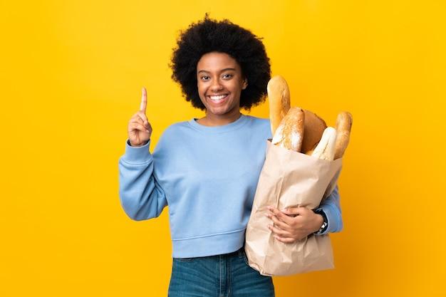 Jonge afrikaanse amerikaanse vrouw die iets brood koopt dat op gele achtergrond wordt geïsoleerd die een geweldig idee benadrukt