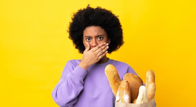 Jonge afrikaanse amerikaanse vrouw die iets brood koopt dat op gele achtergrond wordt geïsoleerd die mond behandelt met hand