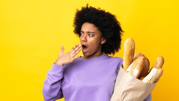 Jonge afrikaanse amerikaanse vrouw die iets brood koopt dat op gele geeuw wordt geïsoleerd en die wijd open mond behandelt met hand