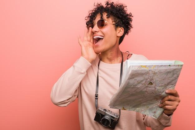 Jonge afrikaanse amerikaanse vrouw die kaart schreeuwen opgewekt aan voorzijde houden.