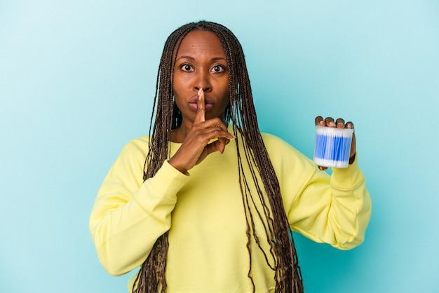 Jonge afrikaanse amerikaanse vrouw die katoenstieren houdt die op knoppenachtergrond worden geïsoleerd die een geheim houden of om stilte vragen.