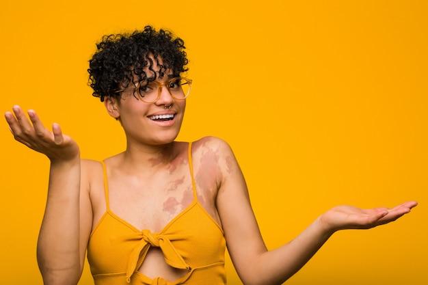 Jonge afrikaanse amerikaanse vrouw die met huidgeboorteteken tussen twee opties twijfelt.