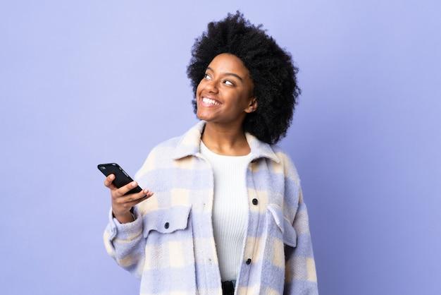 Jonge afrikaanse amerikaanse vrouw die mobiele telefoon met behulp van die op purpere muur wordt geïsoleerd die omhoog terwijl het glimlachen kijkt