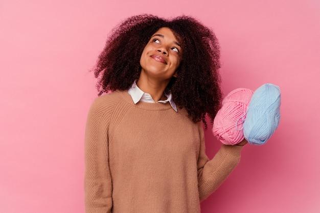 Jonge afrikaanse amerikaanse vrouw die naaiende draden houdt die op roze achtergrond worden geïsoleerd die dromen van het bereiken van doelstellingen en doeleinden
