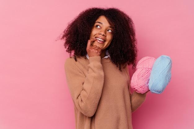 Jonge afrikaanse amerikaanse vrouw die naaiende draden houdt die op roze achtergrond worden geïsoleerd ontspant het denken over iets dat een exemplaarruimte bekijkt.