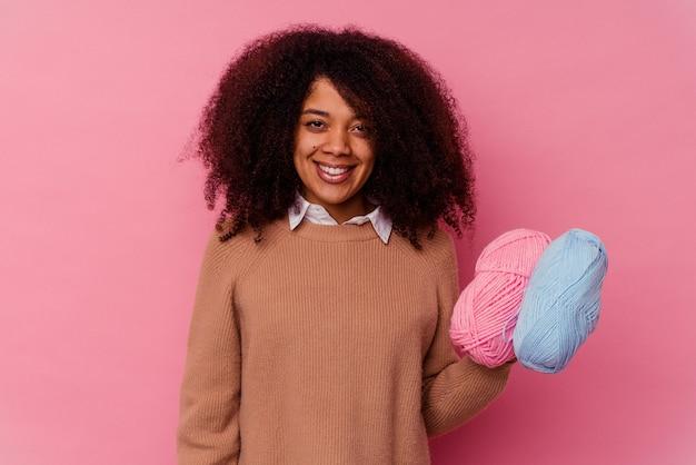 Jonge afrikaanse amerikaanse vrouw die naaiende draden houdt die op roze gelukkig, glimlachend en vrolijk worden geïsoleerd.