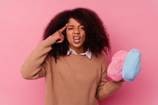 Jonge afrikaanse amerikaanse vrouw die naaiende draden houdt die op roze worden geïsoleerd dat een teleurstellinggebaar met wijsvinger toont.