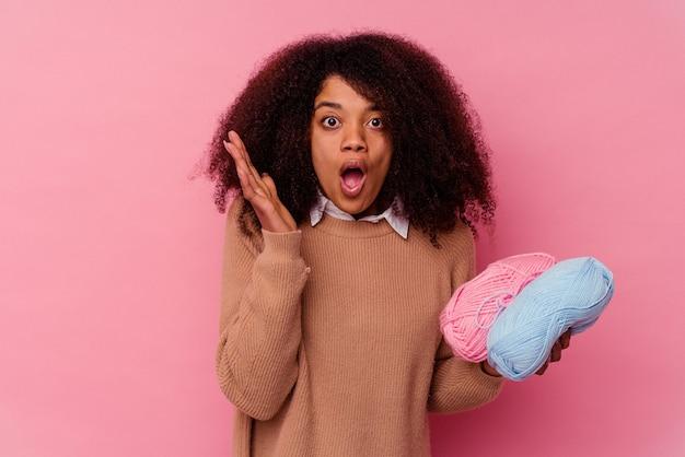 Jonge afrikaanse amerikaanse vrouw die naaiende draden houdt die op verrast en geschokt roze worden geïsoleerd.