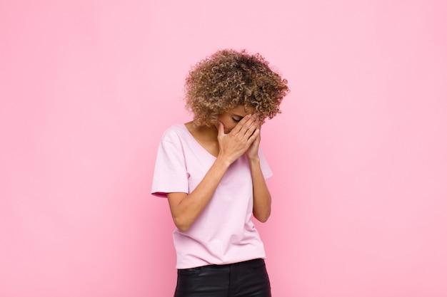 Jonge afrikaanse amerikaanse vrouw die ogen behandelt met handen met een droevige, gefrustreerde blik van wanhoop, huilend, zijaanzicht tegen roze muur