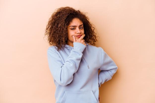 Jonge afrikaanse amerikaanse vrouw die op beige achtergrond wordt geïsoleerd die, een strategie plant, nadenkt over de manier van een bedrijf.