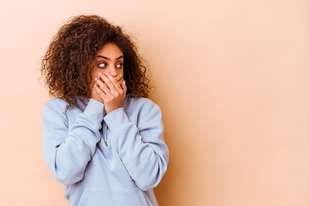 Jonge afrikaanse amerikaanse vrouw die op beige nadenkend aan een exemplaarruimte kijkt die mond behandelt met hand.