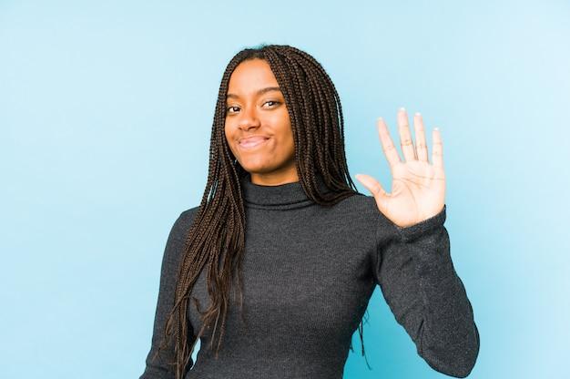 Jonge afrikaanse amerikaanse vrouw die op blauwe achtergrond wordt geïsoleerd die vrolijk tonend nummer vijf met vingers glimlacht.