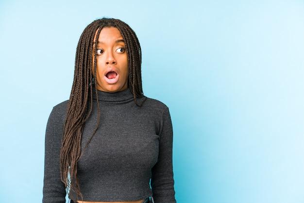 Jonge afrikaanse amerikaanse vrouw die op blauwe achtergrond wordt geïsoleerd die wordt geschokt wegens iets dat zij heeft gezien.