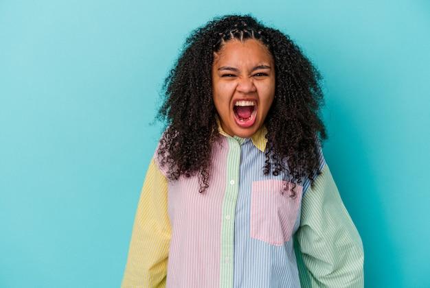 Jonge afrikaanse amerikaanse vrouw die op blauwe achtergrond wordt geïsoleerd die zeer boos, gefrustreerd woedeconcept schreeuwt.